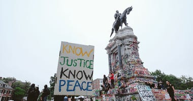 A No justice no peace sign stands at the Robert E. Lee monument on June 20, 2020 in Richmond, Virginia. Protesters for racial justice have called for statues of Confederate leaders, like Lee, be taken down.