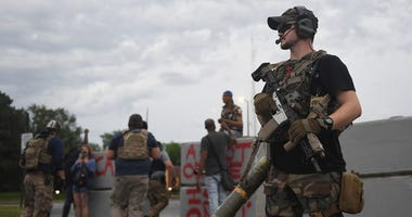 """A group of heavily armed men who identified themselves as the """"People's Protection Group"""" arrive during a protest outside the police department on June 30, 2020 in Florissant, Missouri."""