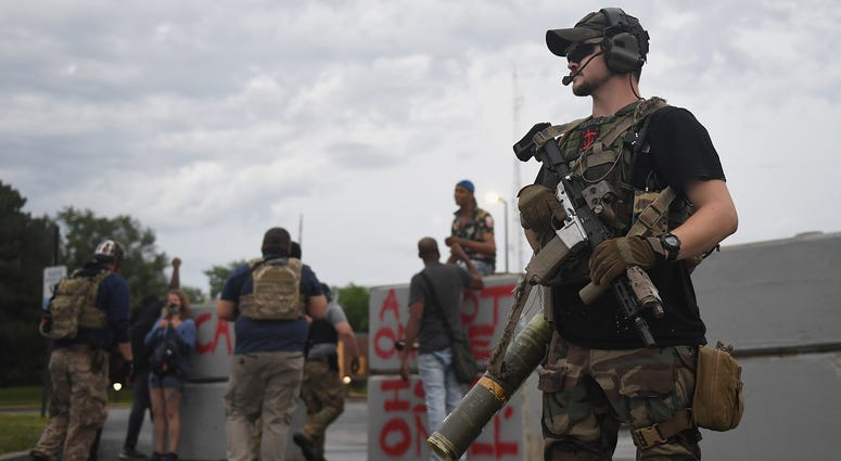 "A group of heavily armed men who identified themselves as the ""People's Protection Group"" arrive during a protest outside the police department on June 30, 2020 in Florissant, Missouri."