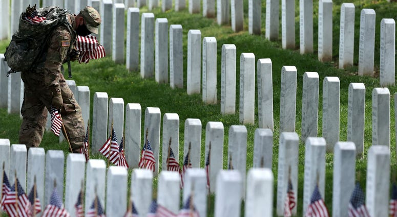 """Wearing face masks to reduce the risk of spreading the novel coronavirus, soldiers from the 3rd Infantry Regiment, also called the """"Old Guard,"""" place U.S. flags in front of every grave site ahead of the Memorial Day weekend in Arlington National Cemetery."""