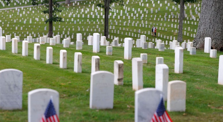 A couple stands amongst the graves in Marietta National Cemetery on Memorial Day, May 25, 2020 in Marietta, Georgia.