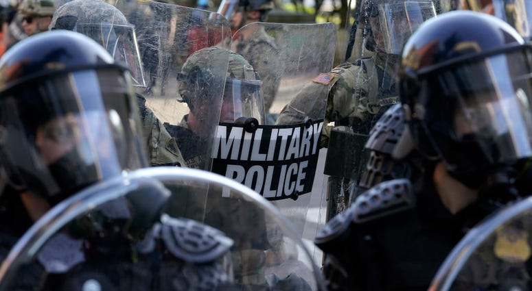 Law enforcement officers and members of the National Guard monitor a protest on June 1, 2020 in downtown Washington, DC.