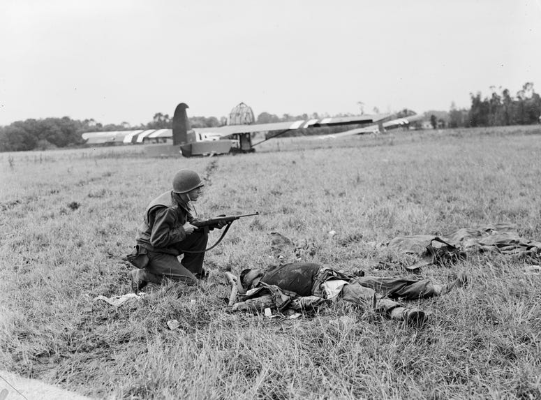1st July 1944: An American soldier crouching by the body of a dead German soldier with US Waco troop carrying gliders on the field behind him in Normandy.