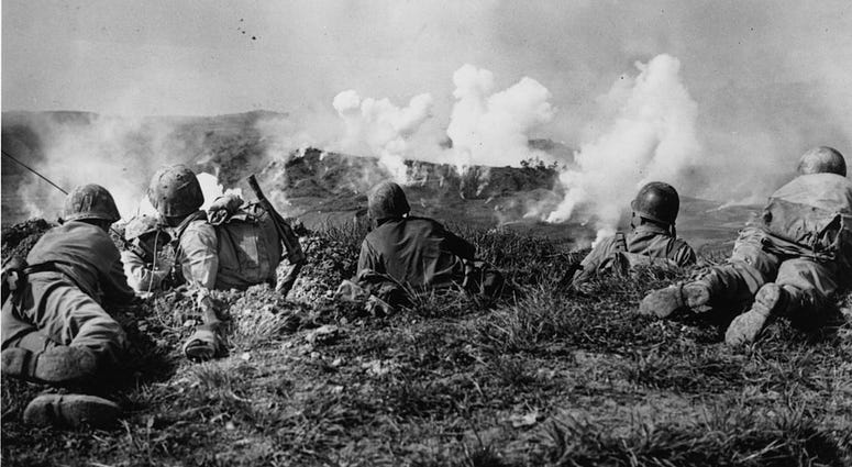 US Marines of the 1st Division wait on the crest of a hill in southern Okinawa, as they watch phosphorous shells explode over Japanese soldiers dug into the hills.