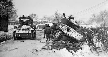 January 1945: Hard going for US tanks at Amonines, Belgium, on the northern flank of the 'battle of the bulge'. A tank on the road passes another being dug out of the snow.