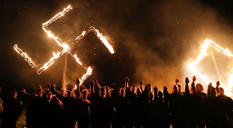 DRAKETOWN, GA - APRIL 21: Members of the National Socialist Movement, one of the largest neo-Nazi groups in the US, hold a swastika burning after a rally on April 21, 2018 in Draketown, Georgia. Community members had opposed the rally in Newnan and came o