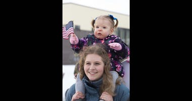 Brynlee, 1, sitting on top of family au pair, Jennifer Rauch, waves an American flag while waiting to greet her father at Joint Base Elmendorf-Richardson, Alaska, Feb. 7, 2020.