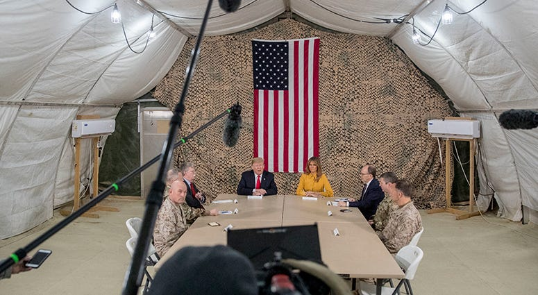 President Donald Trump, accompanied by National Security Adviser John Bolton, third from left, first lady Melania Trump, fourth from right, US Ambassador to Iraq Doug Silliman, third from right, and senior military leadership, speaks to members of the med