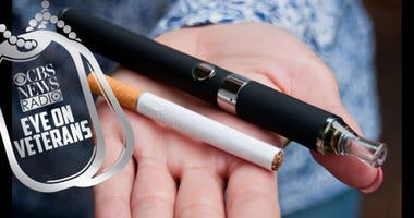 Hand holding e-cig and cigarettes. Doctors warns about vaping