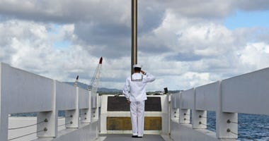 Petty Officer Second Class Derek Loughrey salutes the ensign at the USS Utah Memorial before lowering it to half mast prior to the Richard Laubert's ash shattering ceremony