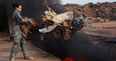 Senior Airman Frances Gavalis, 332nd Expeditionary Logistics Readiness Squadron equipment manager, tosses unserviceable uniform items into a burn pit, March 10.