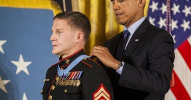 President of the United States, Barrack H. Obama places the Medal of Honor around retired U.S. Marine Corps Cpl. William Kyle Carpenter's neck, inside the East Wing of the White House, June 19, 2014.
