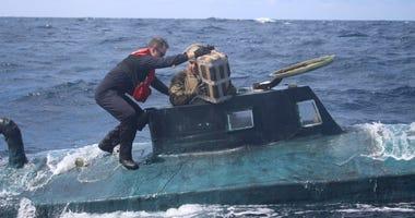 U.S. Coast Guard boarding team members climb aboard a suspected smuggling vessel.