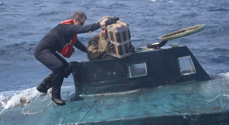 U.S. Coast Guard boarding team members climb aboard a suspected smuggling vessel.