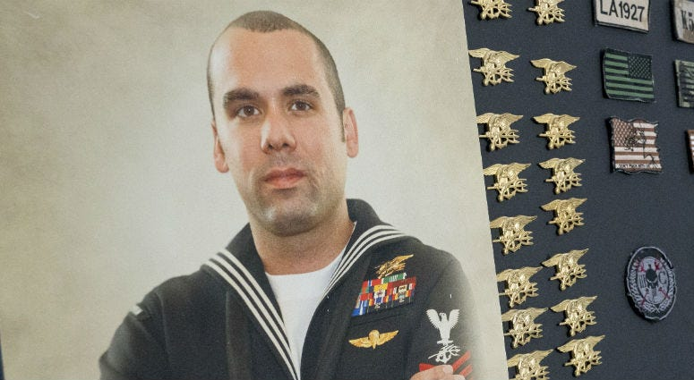In his parents home a photo of Ryan Larkin, a decorated Navy SEAL who committed suicide after suffering from undiagnosed Traumatic Brain Injury, is displayed next to the SEAL Tridents left by comrades on his casket