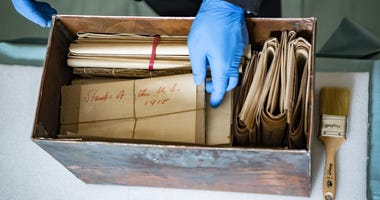 Tim Frank, historian, History Office; reaches into the newly opened Memorial Amphitheater memorabilia box