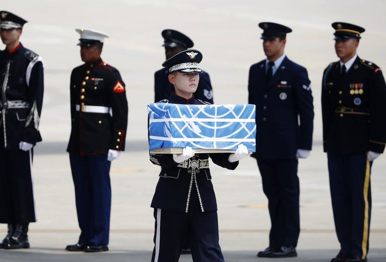 A solider carries a casket carrying what are believed to be the remains of an American service member killed during the Korean War.