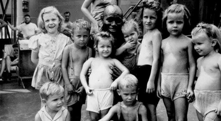 4.Children aboard the SS Jean Lafitte, bound for the States with internees freed from a Japanese internment camp in the Philippines, gather around Pendleton Thompson. Thompson volunteered as cook in the camp where they were interned.