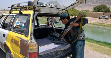 An Afghan policeman checks a vehicle near the Shah Walikot district of Kandahar province, Afghanistan, July 20, 2017.
