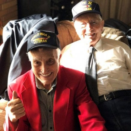 Brothers Ed and Ted Sikora pose for a photo wearing World War II veteran caps