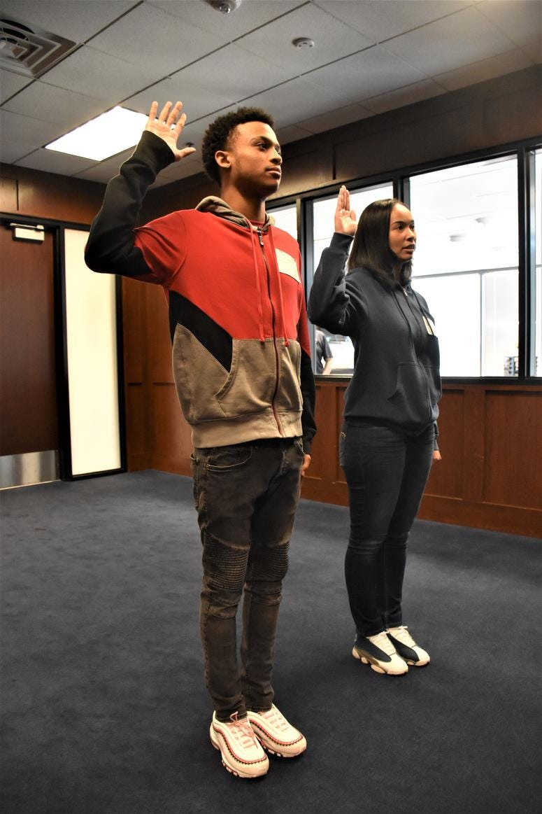 Marquis Butts (left) and his mother, Marva Burns (right), take the oath of enlistment