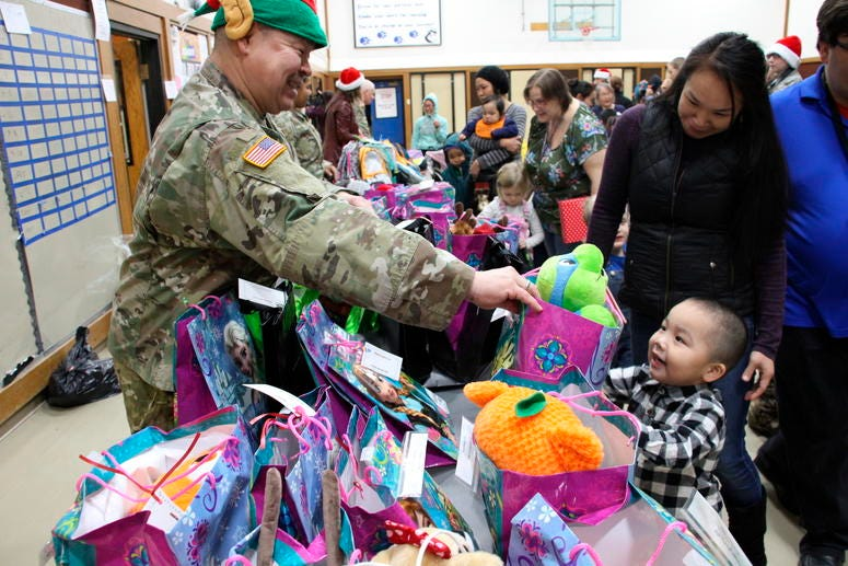 This Dec. 3, 2019, photo shows Alaska National Guard Staff Sgt. Joseph Sallaffie handing a gift bag to Corban Jimmy while Marlene Black looks on during Santa's visit to Napakiak, Alaska.