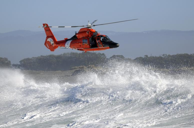 An MH-65 Dolphin helicopter crew from Coast Guard Sector Humboldt Bay conducts search and rescue training in the surf off the coast of Somoa Dunes Beach, Calif