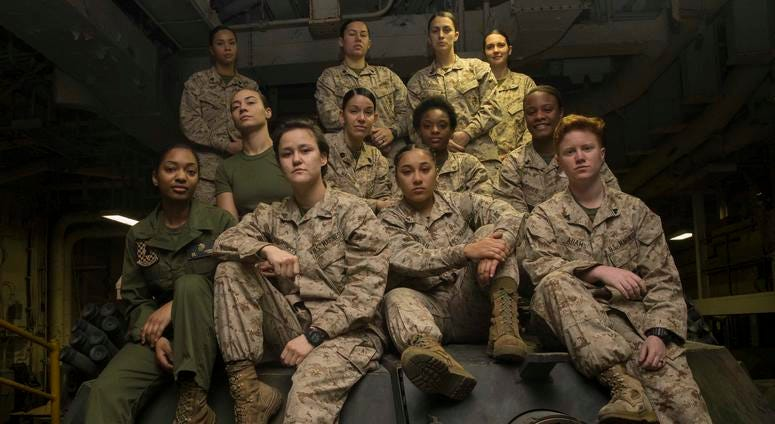 Female Engagement Team Marines pose atop an M1A1 Abrams Main Battle Tank turret after completing training