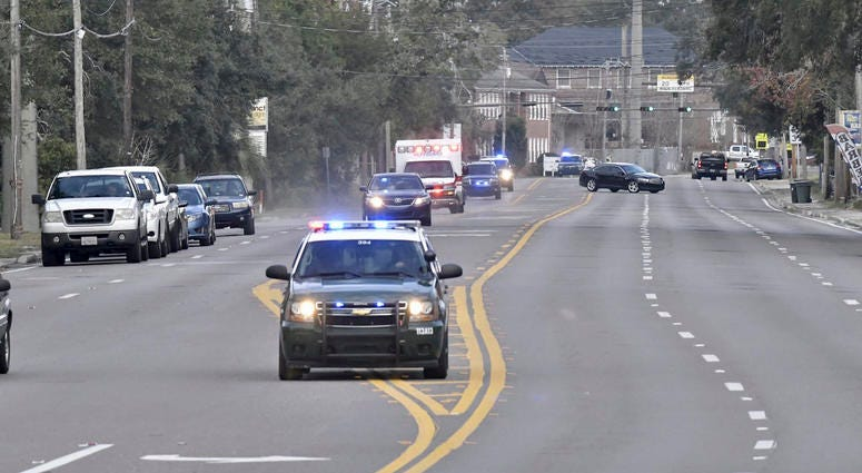 Police cars escort an ambulance after a shooter open fire inside the Pensacola Air Base, Friday, Dec. 6, 2019 in Pensacola, Fla. The US Navy is confirming that a shooter is dead and several injured after gunfire at the Naval Air Station in Pensacola.