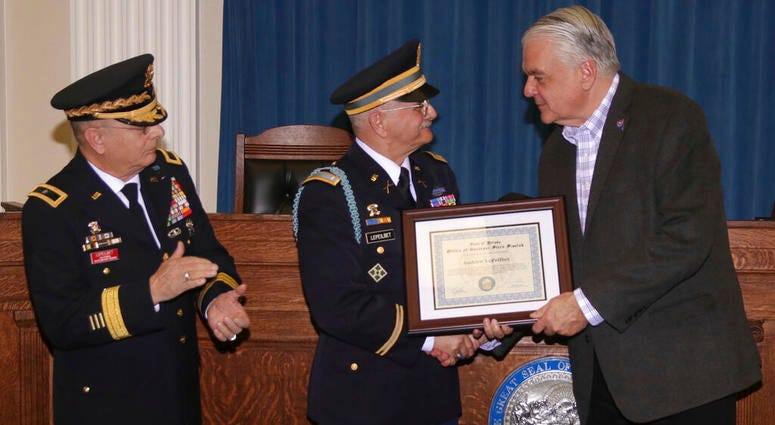 In this Dec. 11, 2019, photo, Army veteran Andrew LePeilbet, center, whose platoon came under heavy fire in Vietnam in 1969, receives a certificate from Gov. Steve Sisolak, right, for a Silver Star medal