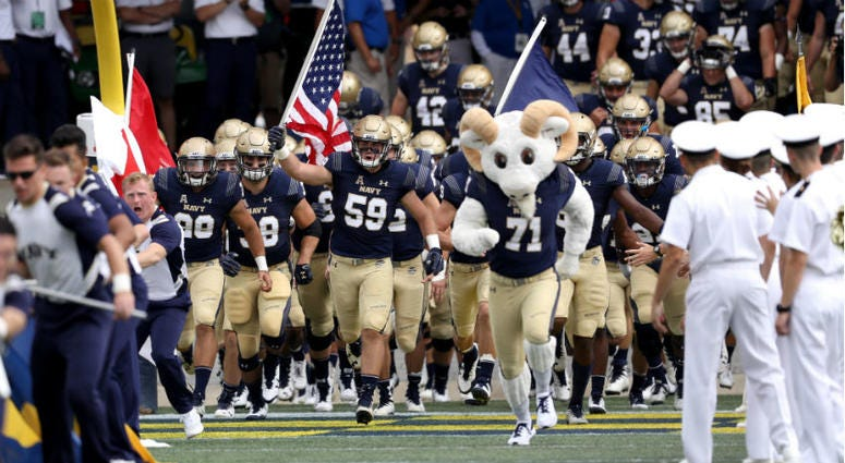 Naval Academy football team changes motto for the season after deeming original insensitive.