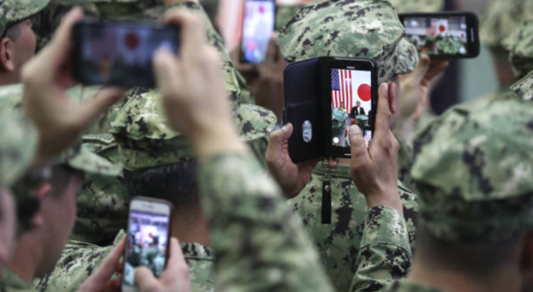 U.S. military personnel use smartphones to take photographs of U.S. President Donald Trump