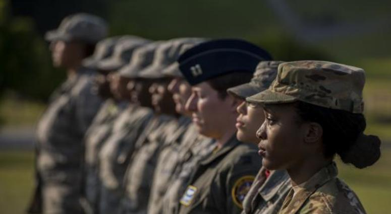 Air Force women at Kadena Air Base stand at attention during womens history month ceremony