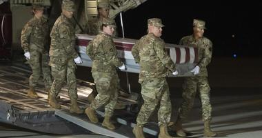 An Air Force carry team moves a transfer case containing the remains of Navy Ensign Joshua Watson