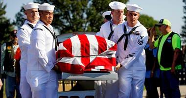 Sailors carry the casket of World War II veteran Herman White