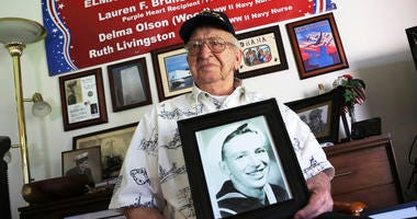 In this Nov. 17, 2016, file photo, Lauren Bruner, a survivor of the USS Arizona which was attacked on Dec. 7, 1941, holds with a 1940 photo of himself at his home in La Mirada, Calif. Divers will place the ashes of Bruner in the wreckage of his ship durin