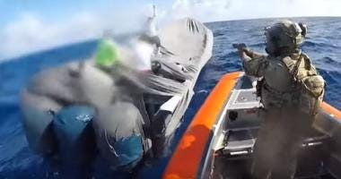 A U. S. Coast Guard boarding team in an interceptor boat deployed from the Coast Guard Cutter Robert Ward (WPC-1130) approaches a suspected drug smuggling vessel in international waters of the Eastern Pacific Ocean July 16, 2019, during a patrol of drug t