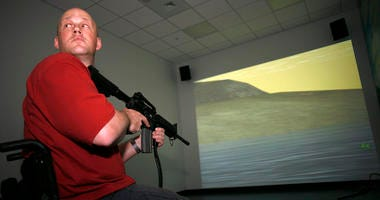 Navy vet Chad Keuser uses a mock M4 assault rifle in simulator at the new high tech Center for the Intrepid rehab center for wounded veterans at Brooke Army Medical Center March 1, 2007 in San Antonio, Texas.