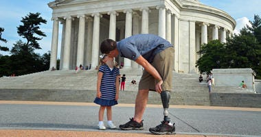 A wounded warrior and his daughter share a kiss in Washintong DC