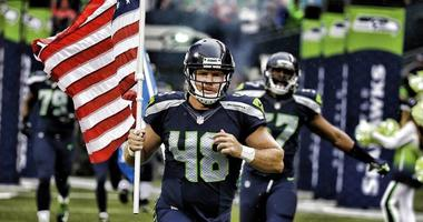 Nate Boyer leads the Seattle Seahawks onto the field carrying the American flag