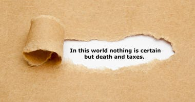 Quote In this world nothing is certain but death and taxes, appearing behind ripped brown paper.