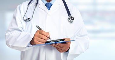 Doctor in white coat holding clipboard