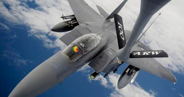 An F-15E Strike Eagle receives fuel from a 100th Air Refueling Wing KC-135 Stratotanker during an aerial refueling mission over the Atlantic Ocean.