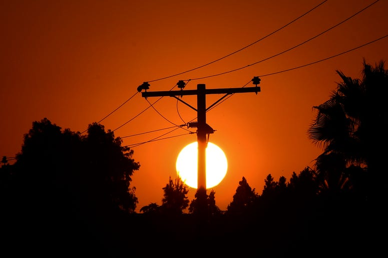 The sun sets behind power lines in Los Angeles, California on September 3, 2020, ahead of a heatwave to arrive September 4 through the Labor Day weekend prompting a statewide flex alert.