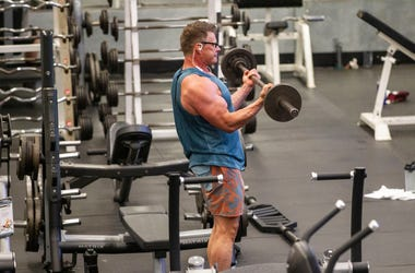 A man lifts a barbell as he works out while being socially distant from others at Momentum Fitness. Gyms Reopening