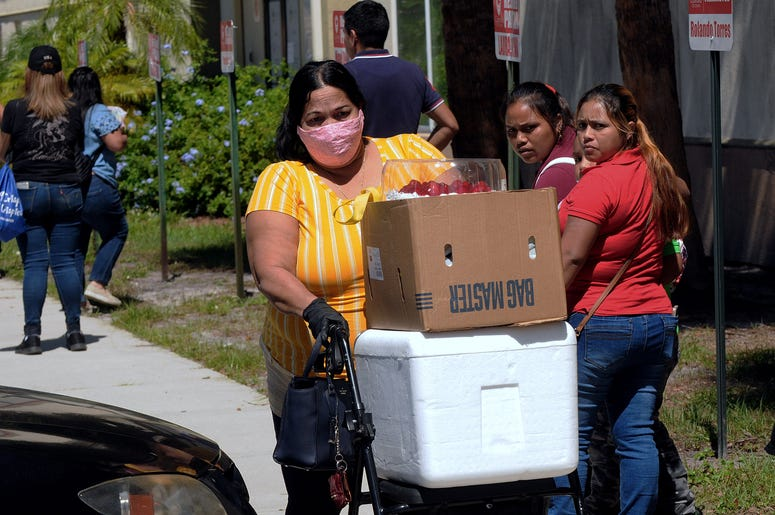 A woman pushes a walker loaded with food assistance provided by the Second Harvest Food Bank of Central Florida at a food distribution event staffed by volunteers at the Calvario City Church. Photo by Paul Hennessy / SOPA Images/Sipa USA)