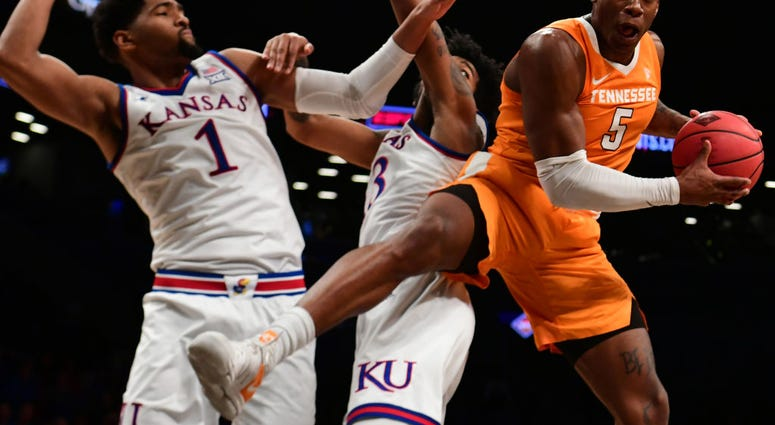 Photo of a Tennessee player being guraded by two Kansas players.