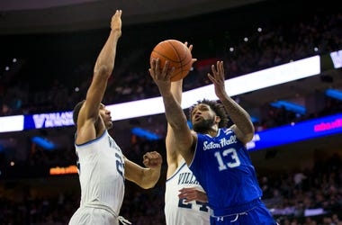 A Seton Hall player goes up for a shot while being guarded by to Villanova players.