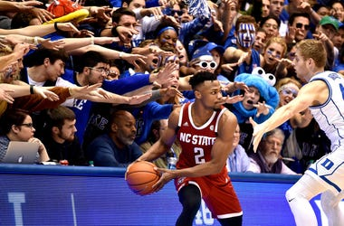 Photo of an NC State player being guarded by a Duke player with Duke fans in the background.