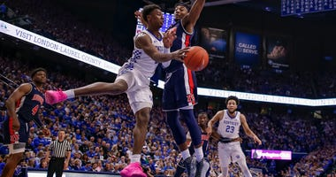 Photo of a Kentucky player attempting to pass around an Auburn player in midair.